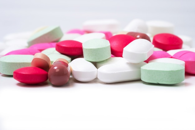 Pilules de médicaments colorés isolés sur fond blanc. concept de soins de santé. Photo Premium