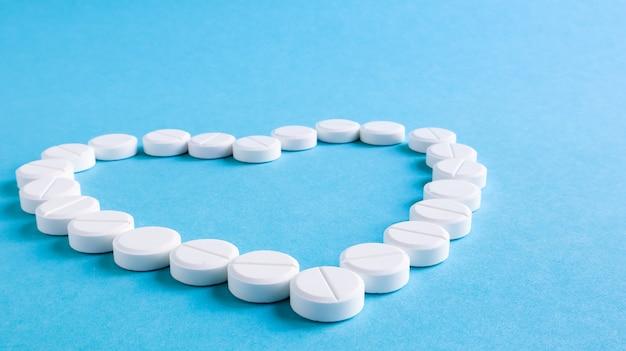 Pilules Rondes Blanches Disposées En Forme De Coeur Sur Fond Bleu. Photo Premium