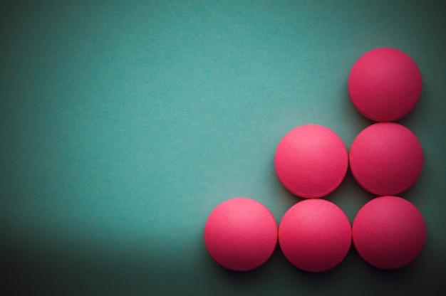 Pilules roses disposées sur un fond vert. Photo Premium