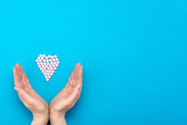 Des Pilules Roses En Forme De Coeur Sur Fond Bleu Et Des Mains Féminines Entourent Un Coeur Fait De Pilules. Photo Premium