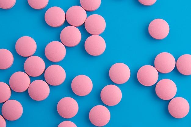 Pilules roses sur la vue de dessus de fond bleu Photo Premium