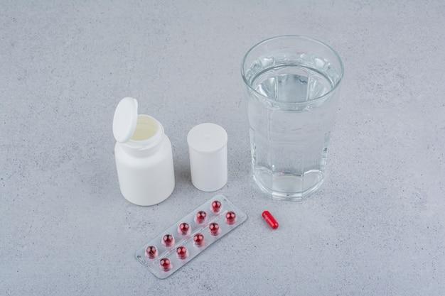 Pilules Rouges, Récipients Et Verre D'eau Sur Une Surface En Marbre. Photo gratuit