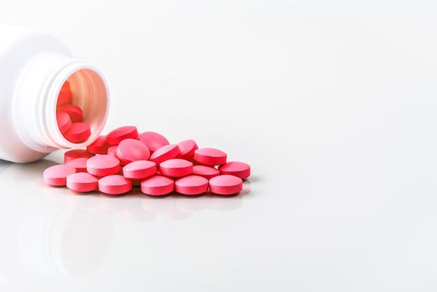 Les pilules rouges sont dispersées à partir d'un pot Photo Premium
