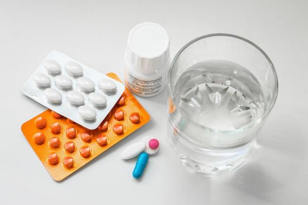 Pilules sous blister, capsules, un verre d'eau sur fond blanc. préparations pour le traitement du rhume, des vitamines, du complexe de bien-être Photo Premium