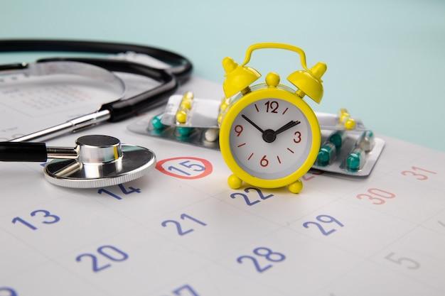 Pilules, Stéthoscope, Réveil Et Calendrier Sur Une Table, Programme Pour Vérifier Le Concept Sain. Photo Premium