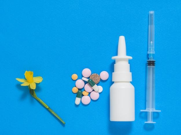 Pilules, vaporisateur nasal et une seringue avec une fleur sur fond bleu Photo Premium