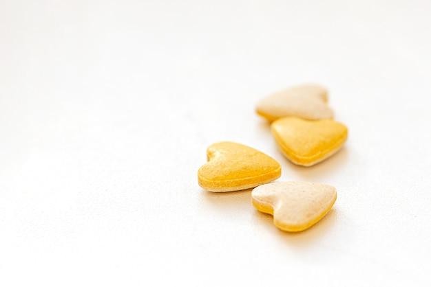 Pilules De Vitamine Jaune En Forme De Coeur Sur Une Surface Blanche Photo Premium