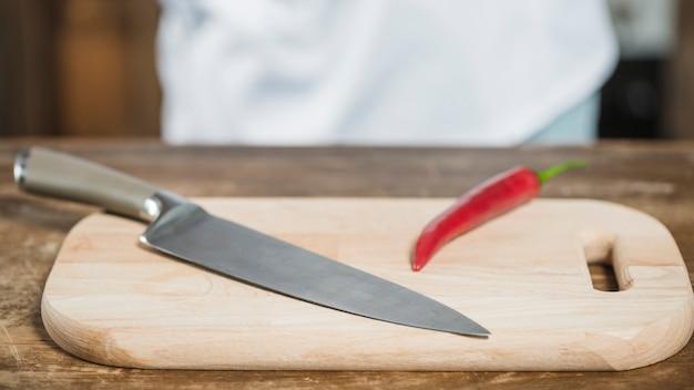 Piment rouge épicé et couteau pointu sur planche à découper Photo gratuit