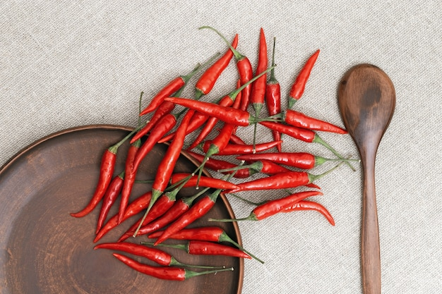 Piments rouges chauds dispersés d'une assiette sur la table. Photo Premium