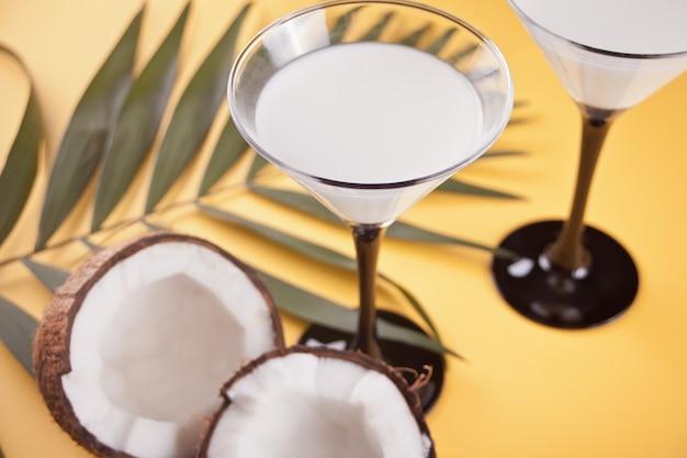 Pina colada cocktail sur la table jaune avec feuille de palmier et noix de coco sur le fond Photo Premium