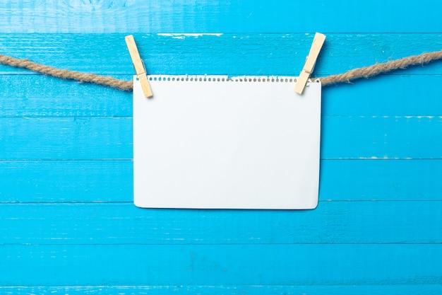 Pince à linge suspendu avec du papier blanc sur fond en bois Photo Premium