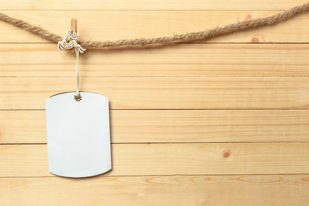 Pince à Linge Suspendu Avec Du Papier Vierge Sur Fond De Bois Photo Premium