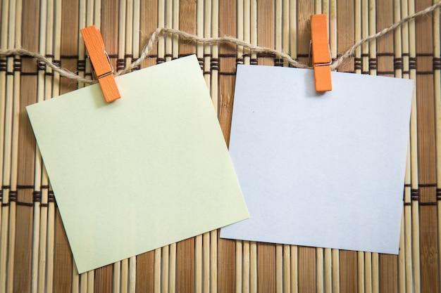 Pince à linge suspendu avec papier blanc sur la texture de fond en bois. Photo Premium