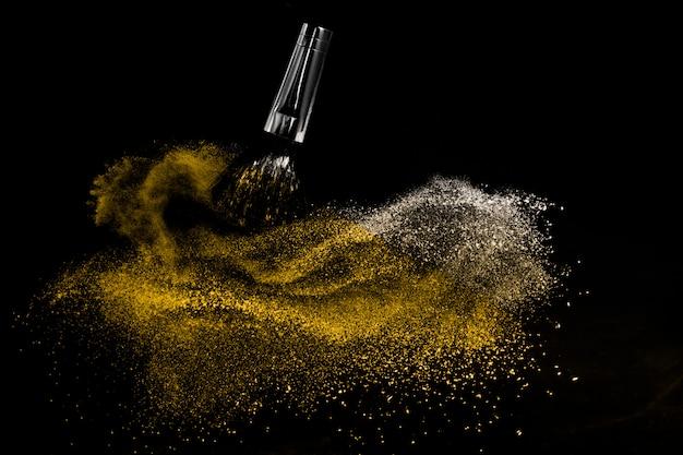 Pinceau cosmétique avec poudre cosmétique dorée se répandant pour maquilleuse et graphisme sur fond noir Photo Premium