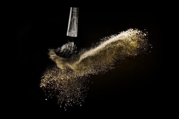 Pinceau cosmétique avec poudre cosmétique dorée Photo Premium