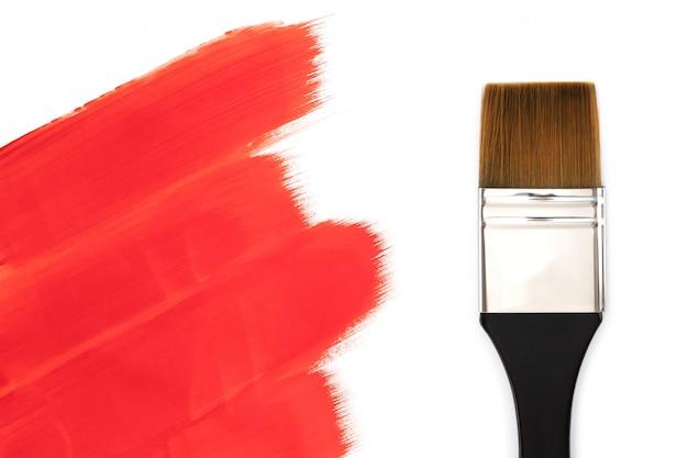 Pinceau et coups de peinture rouge. isolé sur fond blanc Photo Premium