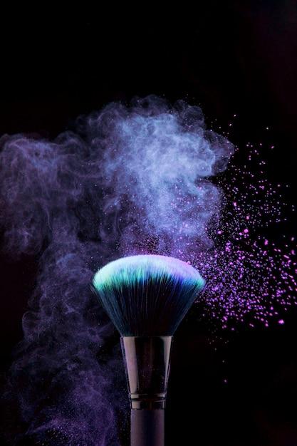 Pinceau de maquillage avec éclaboussure de poudre bleue Photo gratuit