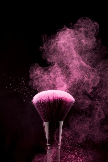 Pinceau de maquillage avec éclaboussures de poudre rose scintillante Photo gratuit