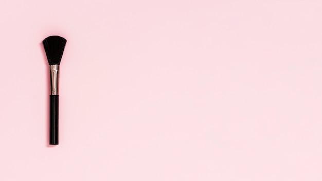 Pinceau de maquillage noir sur fond rose Photo gratuit