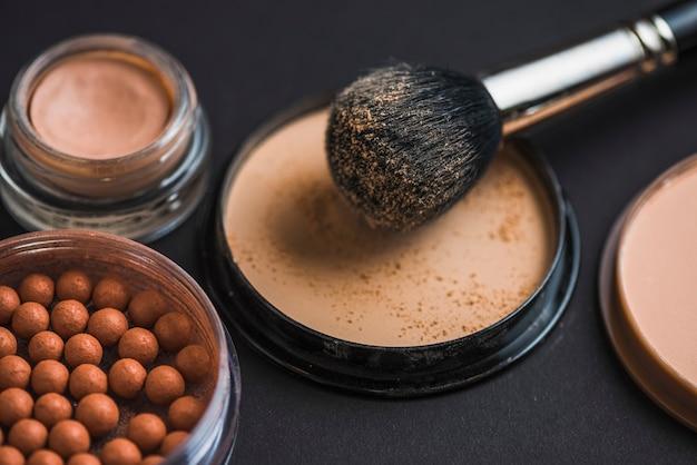 Pinceau de maquillage en poudre compacte avec des perles bronzantes Photo gratuit
