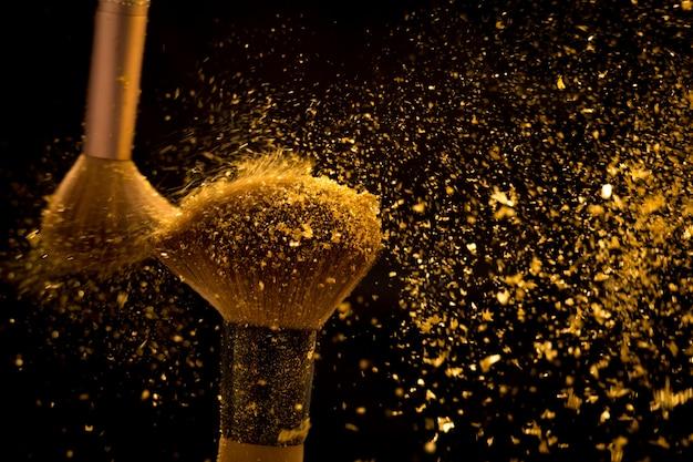 Pinceau de maquillage avec poudre cosmétique dorée se répandant sur fond noir Photo Premium