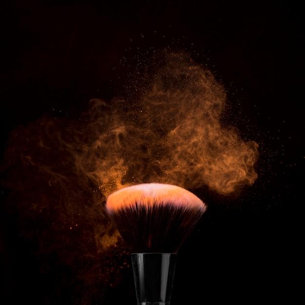 Pinceau à maquillage en poudre éclaté sur fond sombre Photo gratuit