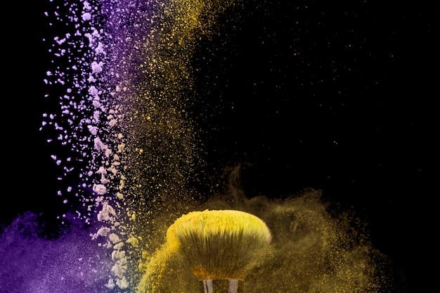 Pinceau de maquillage et poussière de poudre sur fond sombre Photo gratuit