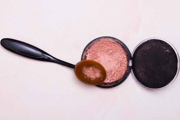 Pinceau ovale et poudre compacte pour le visage isolée sur fond blanc Photo gratuit