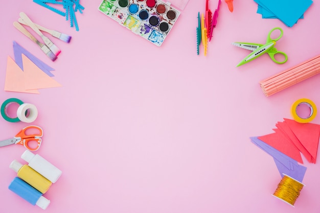 Pinceau; palette de couleurs; ciseaux; bobine d'or; papier et ciseaux sur fond rose Photo gratuit