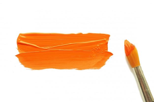 Un pinceau en peinture orange et une tache de peinture acrylique orange sur une feuille de papier vierge blanche. Photo Premium