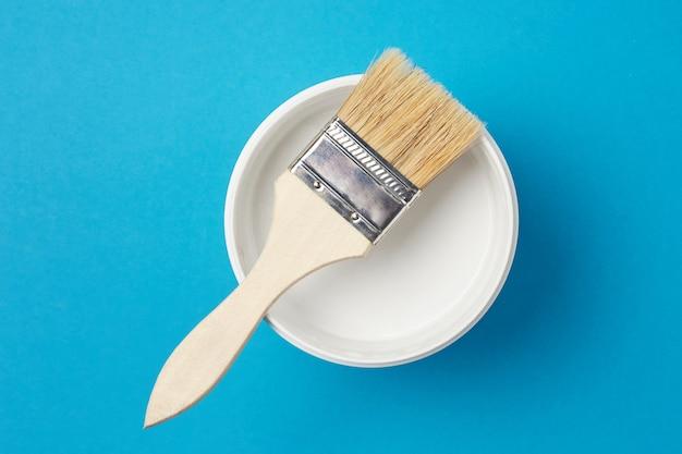 Pinceau Et Peinture Peut Avec La Couleur Blanche Sur Un Fond Bleu, Gros Plan Photo Premium