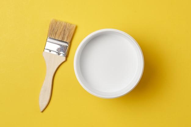 Pinceau Et Peinture Peut Avec La Couleur Blanche Sur Un Fond Jaune, Vue De Dessus Photo Premium