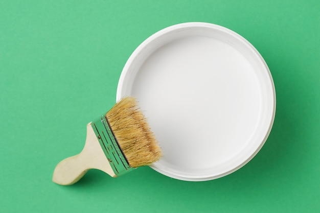 Pinceau Et Peinture Peut Avec La Couleur Blanche Sur Un Fond Vert, Vue De Dessus Photo Premium