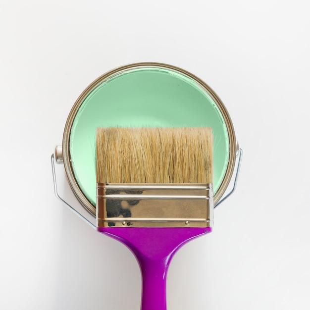 Pinceau violet avec un pot de peinture à la menthe ouvert Photo Premium