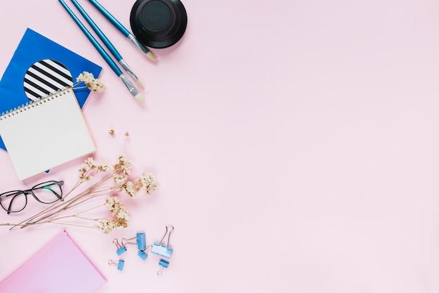 Pinceaux bleus et papeterie avec des fleurs blanches sur fond rose Photo gratuit