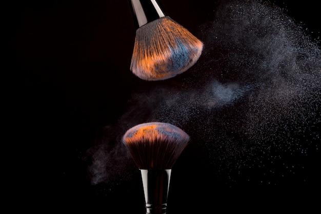 Pinceaux cosmétiques avec brouillard de poudre sur fond sombre Photo gratuit