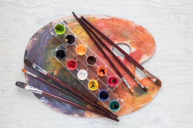 Pinceaux et gouache sur palette Photo gratuit