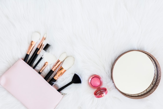 Pinceaux de maquillage dans le sac avec poudre compacte rose et miroir rond sur fond de fourrure Photo gratuit