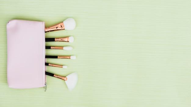 Pinceaux de maquillage à l'intérieur du sac ouvert sur fond vert menthe Photo gratuit