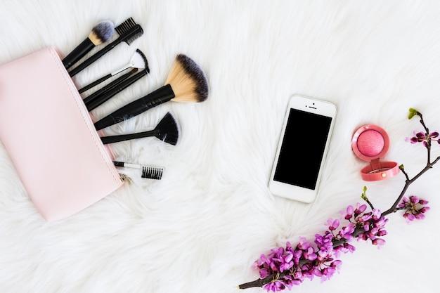 Pinceaux de maquillage avec smartphone; poudre faciale compacte et rameau de fleurs sur fourrure blanche Photo gratuit