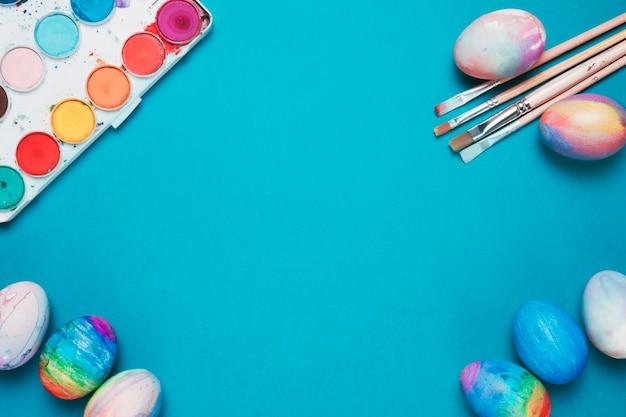 Pinceaux; oeufs de pâques et boîte aquarelle colorée sur fond bleu avec un espace au centre Photo gratuit