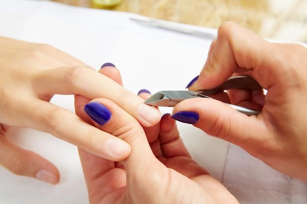 Pinces à cuticules dans les mains de femme Photo Premium