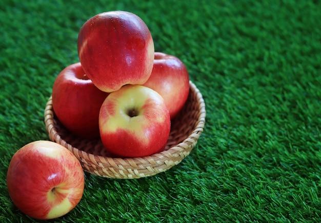 Un Pique-nique Aux Pommes Rouges Et Jaunes Dans Un Panier Sur L'herbe Photo Premium