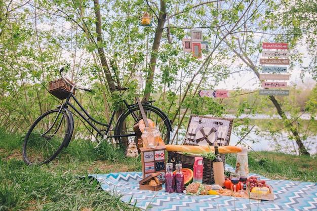 Pique-nique d'été design dans la nature. sur le plaid est un panier de nourriture. Photo Premium