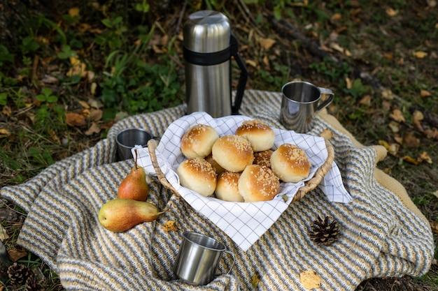 Pique-nique en plein air. thermos avec thé café, délicieux petits pains Photo Premium