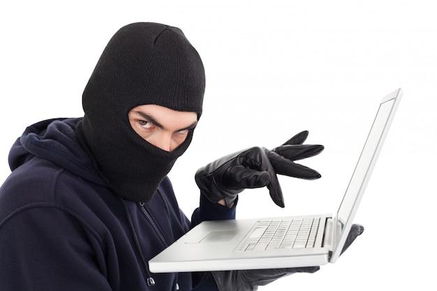 Pirate en cagoule debout et en tapant sur un ordinateur portable sur fond blanc Photo Premium