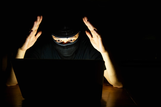 Pirate informatique faisant son travail avec un ordinateur portable dans la pièce sombre Photo gratuit