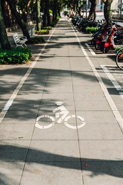 Piste cyclable sur un sentier avec lumière et ombre d'arbres à taipei, taiwan. Photo Premium