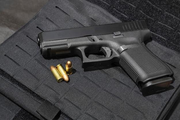 Pistolet et balles de 9 mm sur un gilet pare-balles Photo Premium