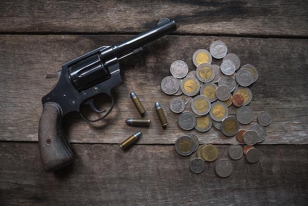 Pistolet et pièces de monnaie sur la table en bois. vue de dessus Photo Premium